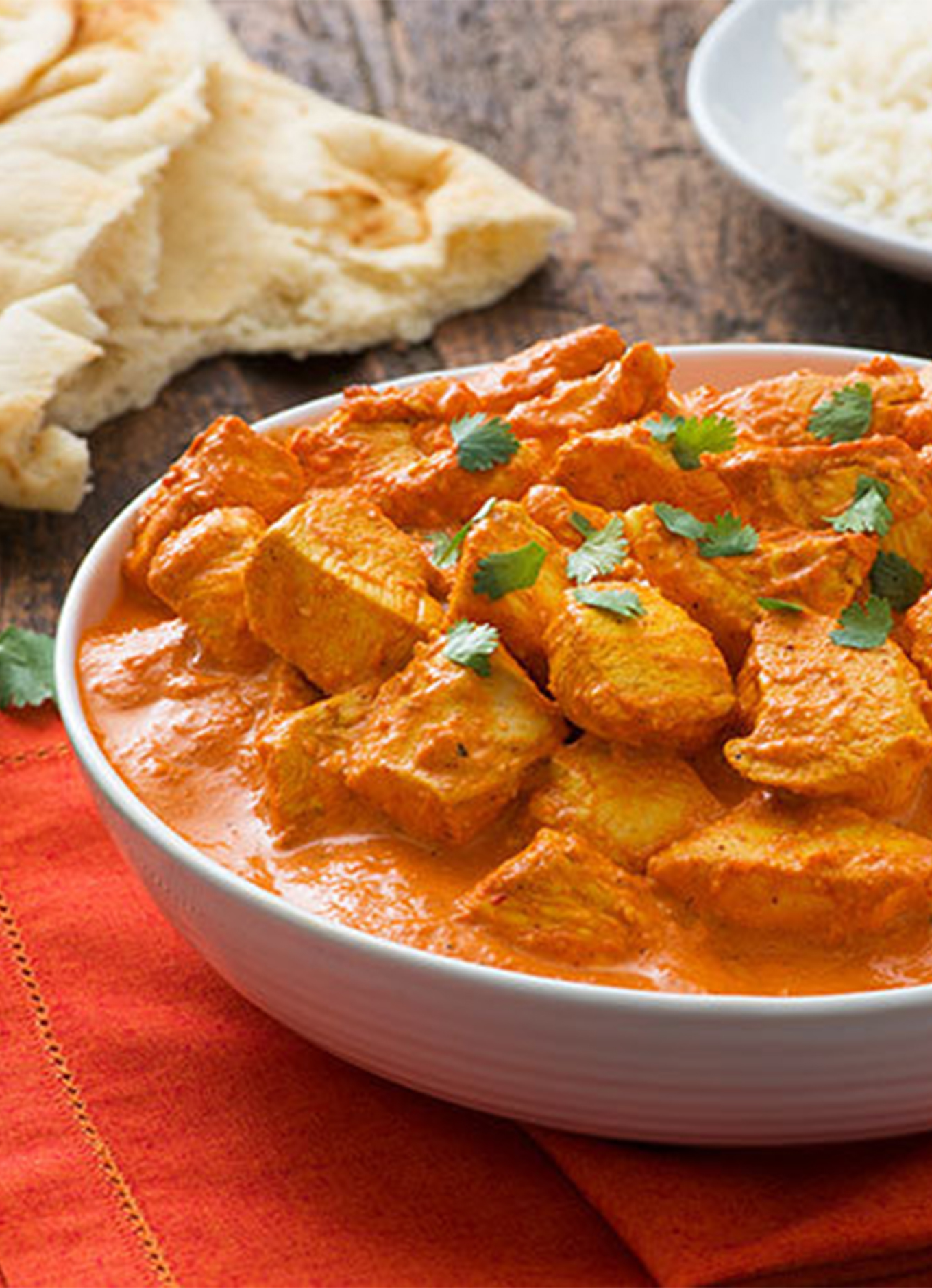 A bowl filled with steaming Chicken Tikka Masala served with a side of naan and rice.
