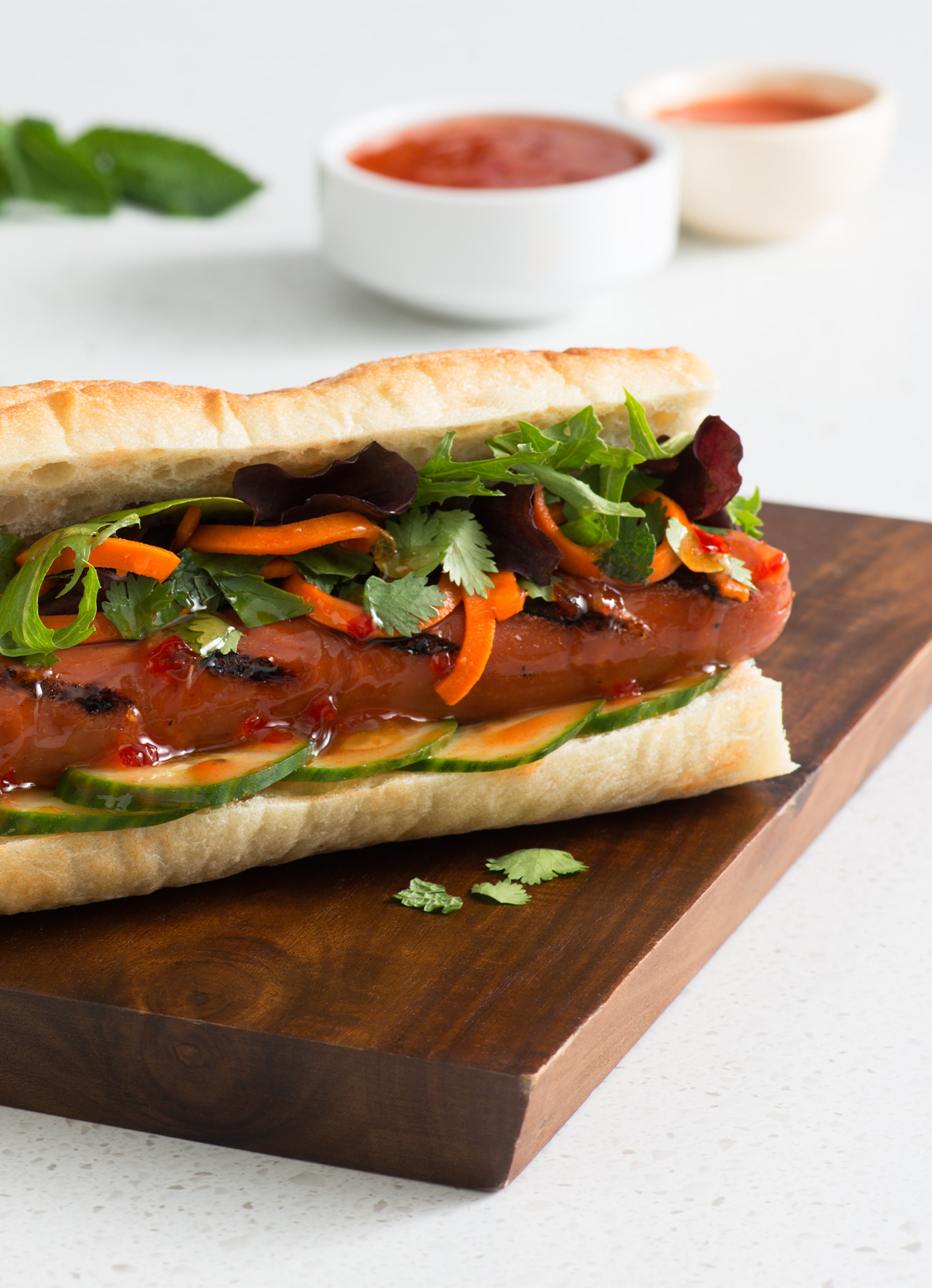 Two Bahn Mi Hot Dogs, topped with cucumber, carrot and salad greens, on a wooden tray.