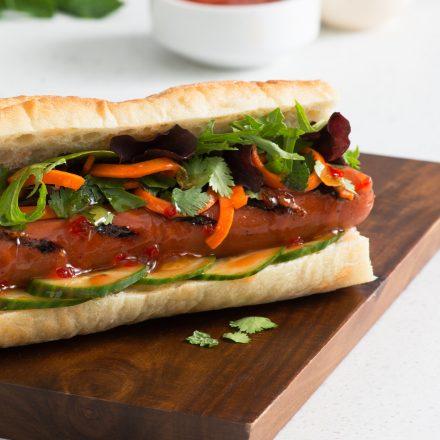 Deux hot-dogs façon Banh Mi, garnis de concombre, de carotte et de feuilles de salade, déposés sur un plateau de bois.
