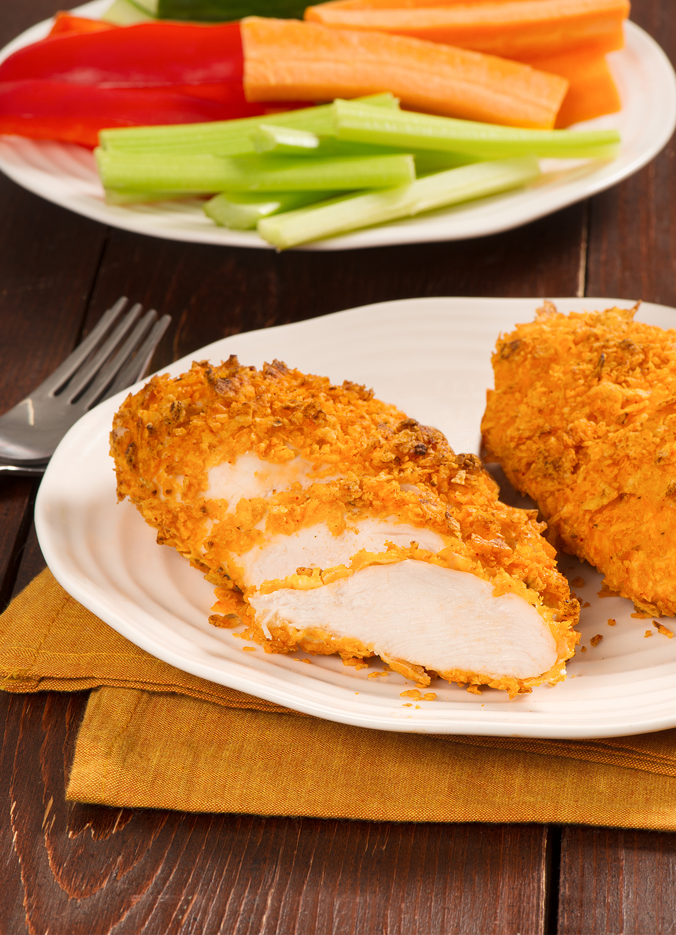 Chicken breasts coated with a crust made of nacho cheese flavoured chips on a table set for a meal.