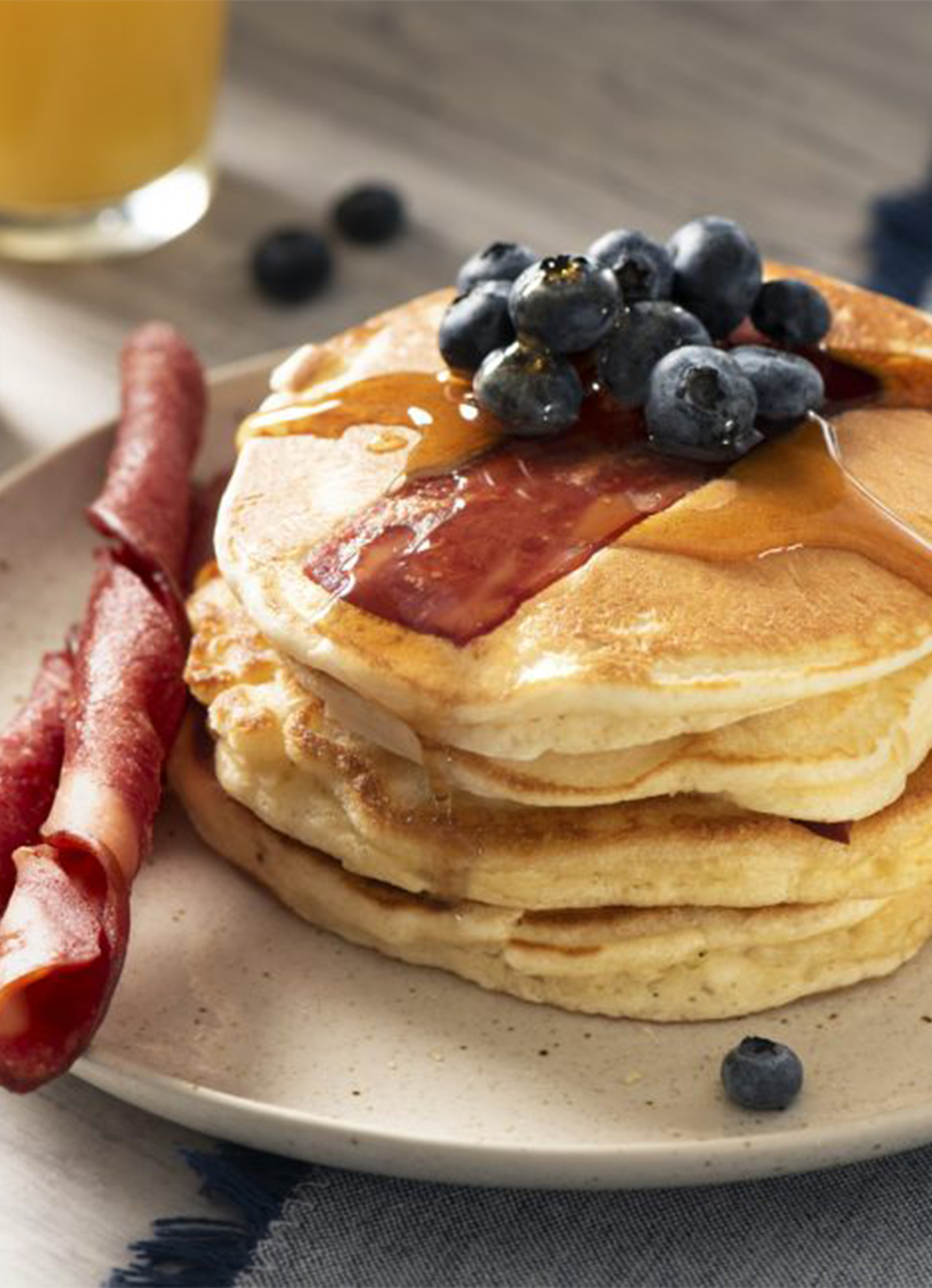 A stack of fluffy flapjacks served with syrup, fresh blueberries, and Breakfast Chicken Strips