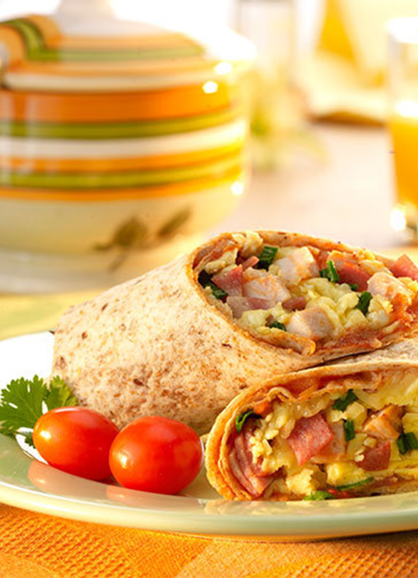 A sunny breakfast table setting with orange juice and aplated breakfast burrito served with fresh vegetables