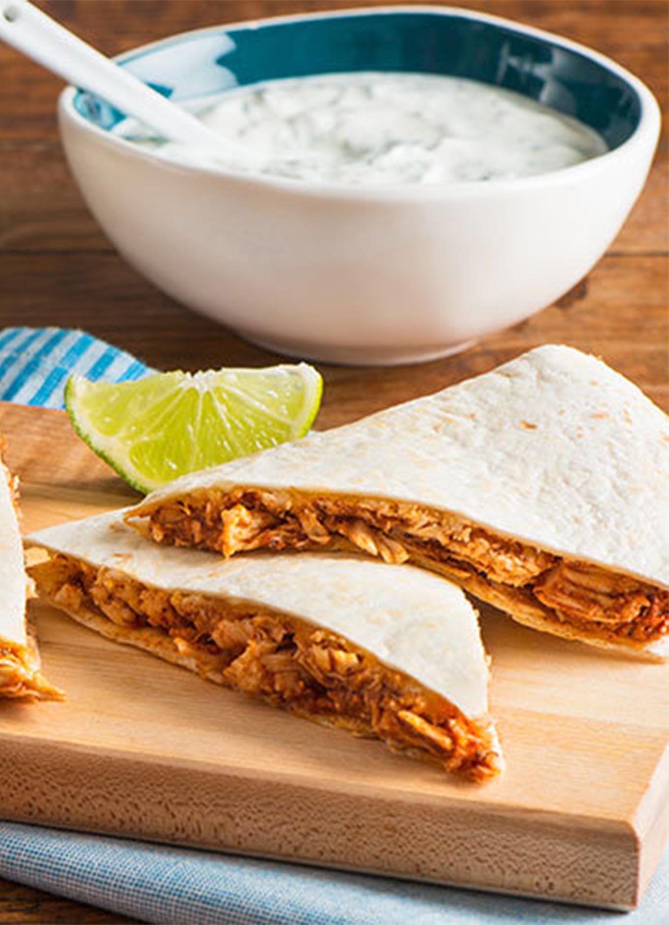 Des quesadillas de poulet servies sur une planche avec un quartier de lime et accompagnées d'une trempette yogourt et menthe