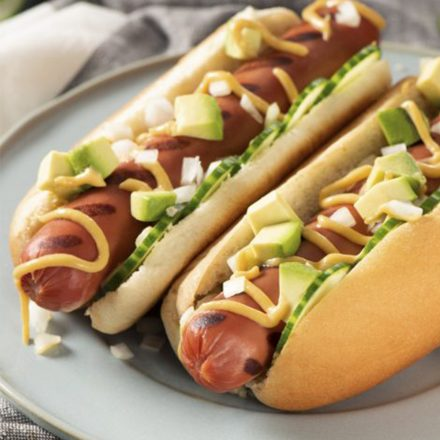 Two hot dogs in toasted buns topped with diced onion, avocado and honey mustard