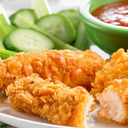 A plate of Chicken strips coated with cheesy fish crackers, served with fresh veggies and dipping sauce