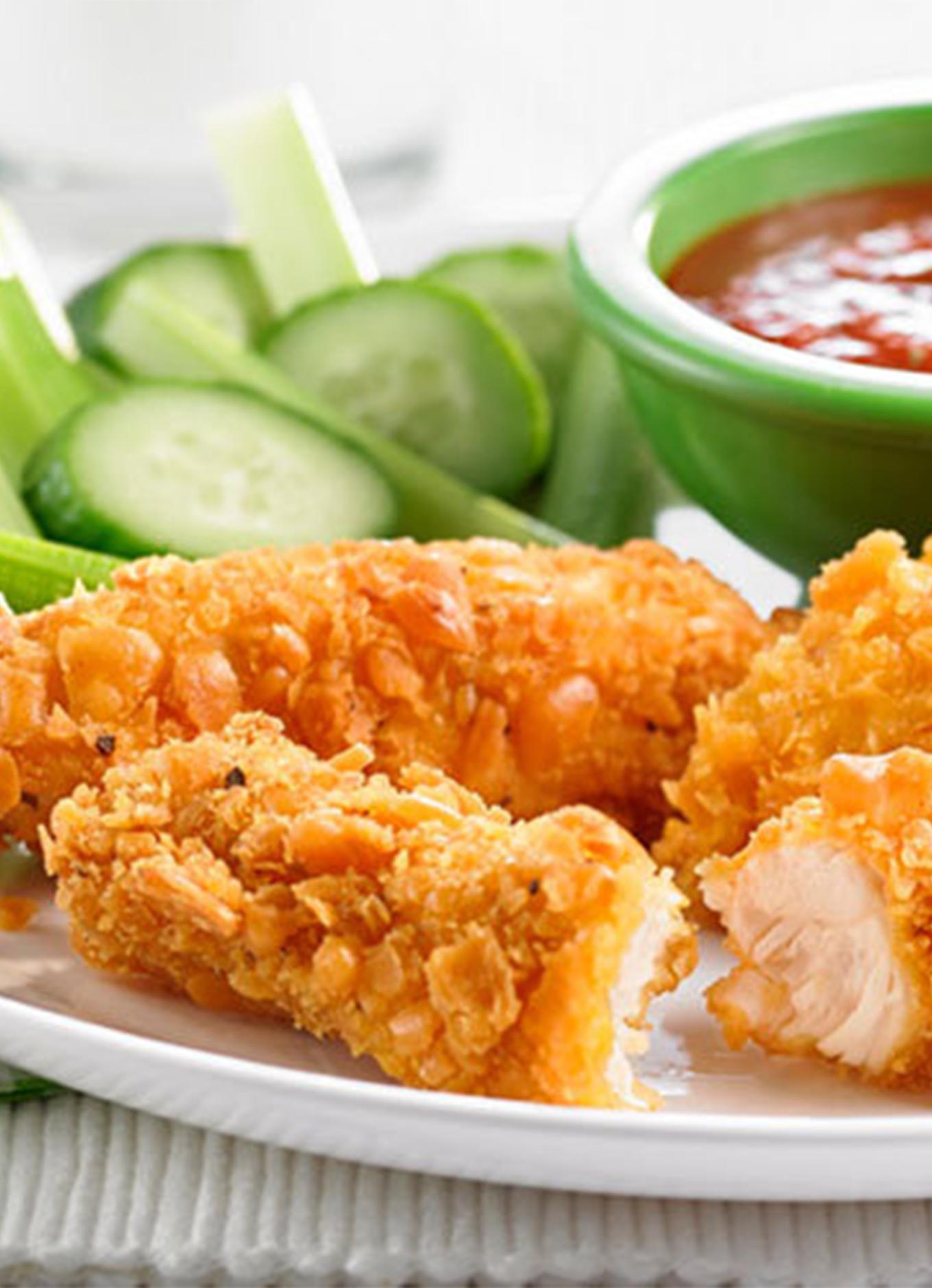 Un plateau de lanières de poulet panées à la chapelure de craquelins de petits poissons au fromage et servies avec des crudités et une trempette