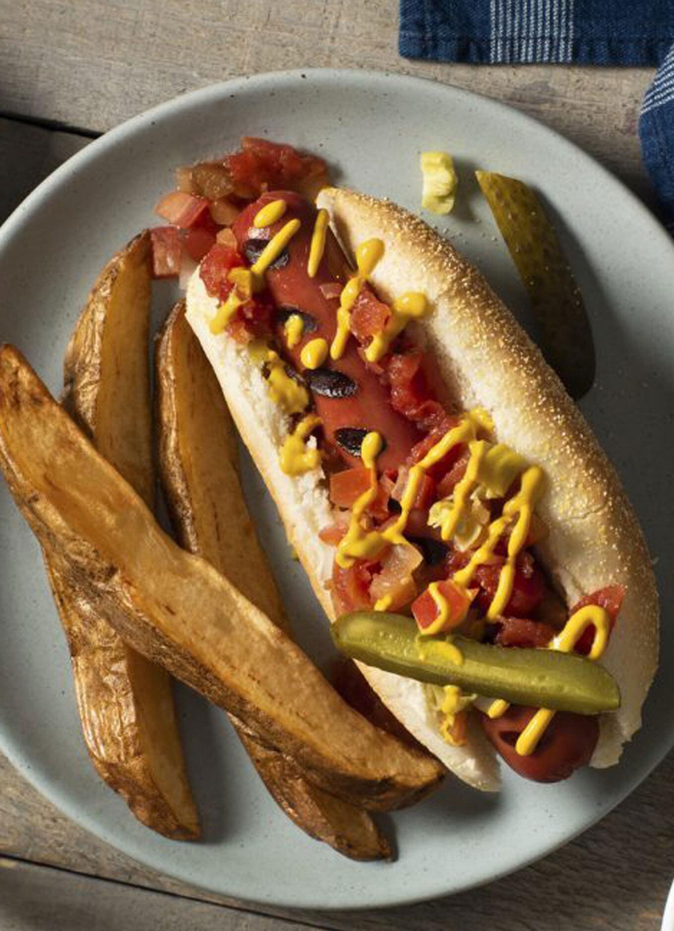 Une saucisse dans un pain grillé, garnie de moutarde, de tomate et d'oignons sautés, avec des quartiers de pomme de terre.