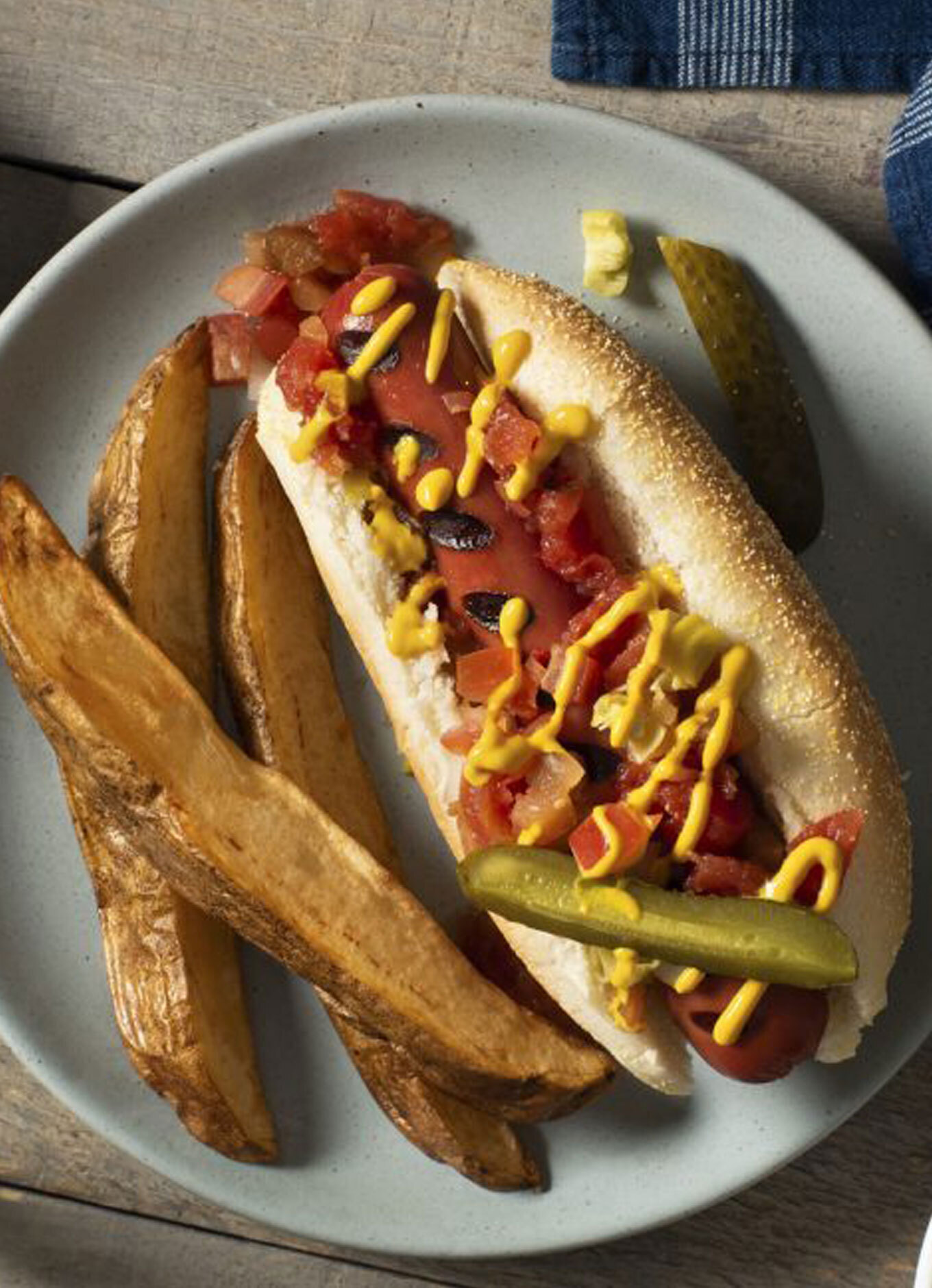 A hot dog on a toasted bun, topped with mustard, tomato, onion and sautéed onion, with a side of potato wedges.