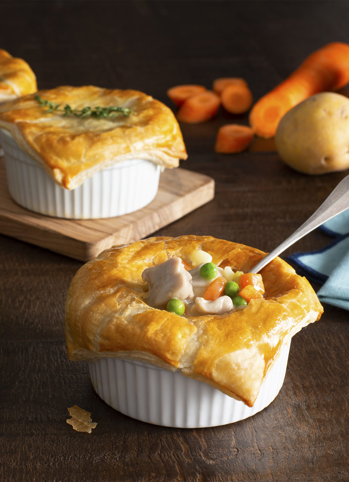 A tray of 3 mini Chicken Pot Pies with golden crusts in white ramekins. The first pie has a spoon in it, showing the chicken and vegetable filling.