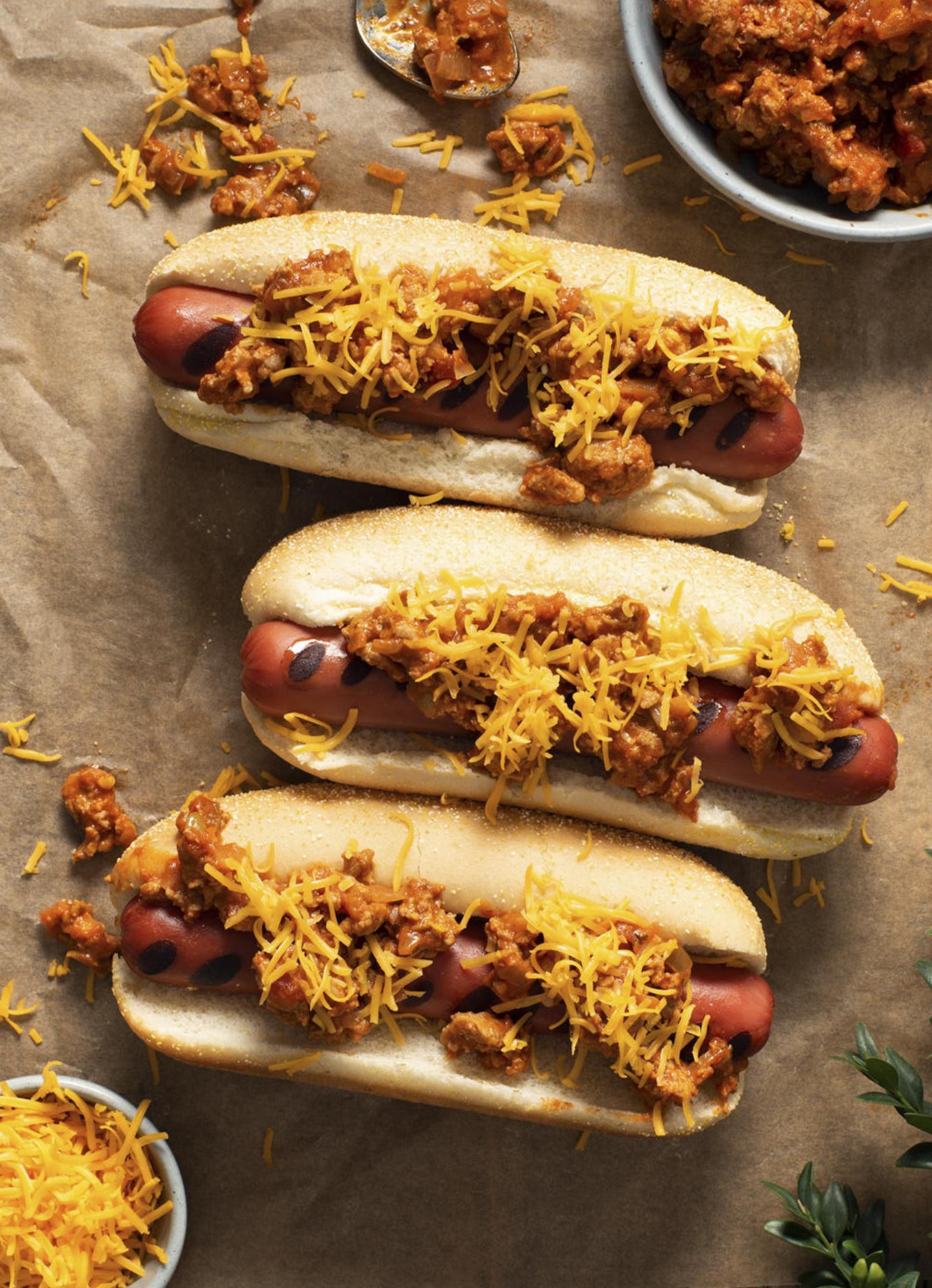 Trois hot-dogs lovés dans des pains grillés, garnis de chili et de fromage fondu, placés sur une feuille de papier parchemin et entourés d'aliments