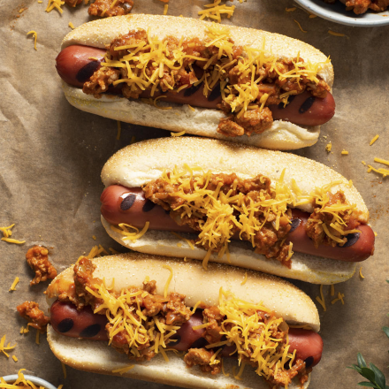 Three hot dogs in toasted buns topped with chili and melted cheese on a sheet of parchment paper, surrounded by ingredients