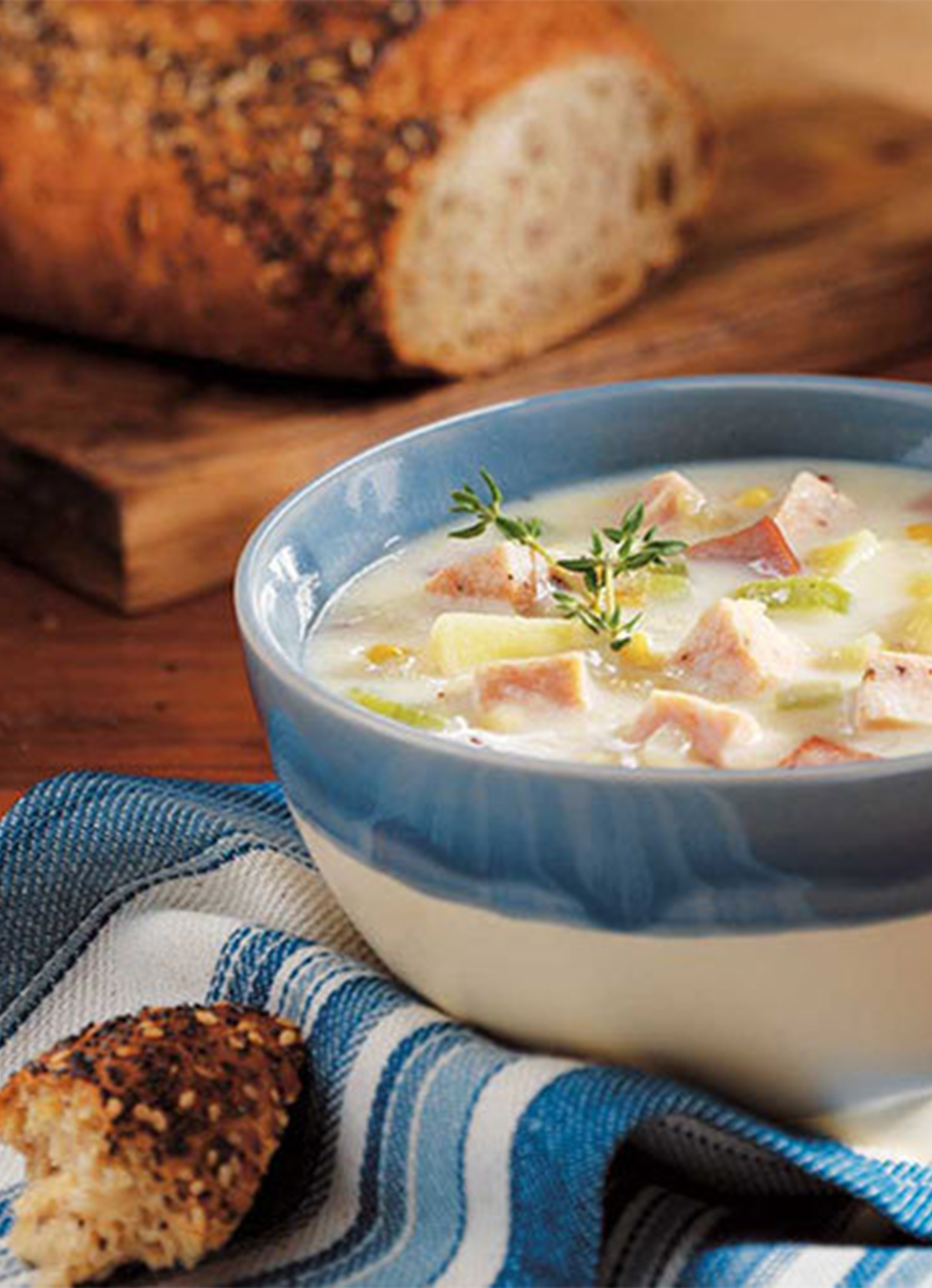 A bowl of Chicken & Corn Chowder on a table with freshly baked bread.