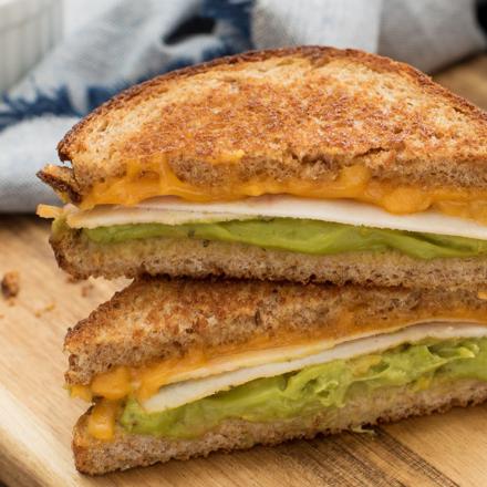 Une section transversale d'un sandwich au fromage grillé avec poulet et guacamole sur une planche à découper en bois montrant les tranches de charcuterie, la couche de guacamole et le fromage fondu