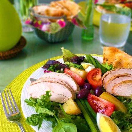 Une salade niçoise avec des poitrines de poulet Zabiha Halal et des légumes frais, reposant sur une table colorée