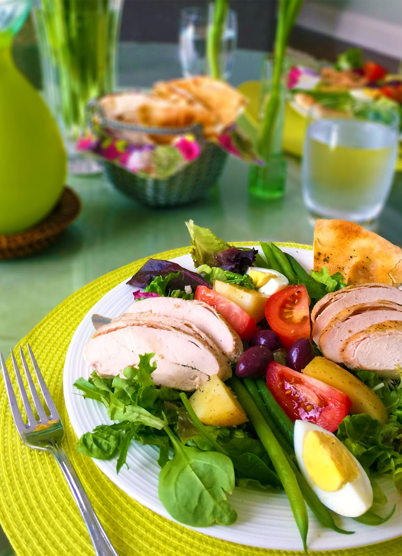 A Nicoise salad made with Zabiha Halal Chicken Breasts and fresh vegetables, on a colourful table.
