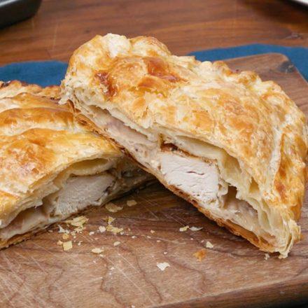 Une pâte feuilletée garnie de poulet, de fines herbes, de canneberges et de fromage à la crème reposant sur une table festive.