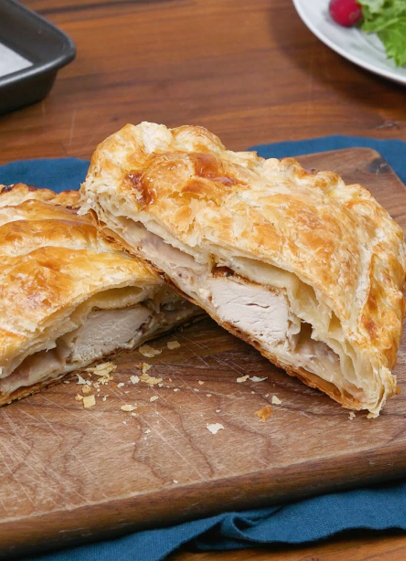 Flaky pastry filled with Chicken, herbs, cranberries, and cream cheese on a festive table setting.