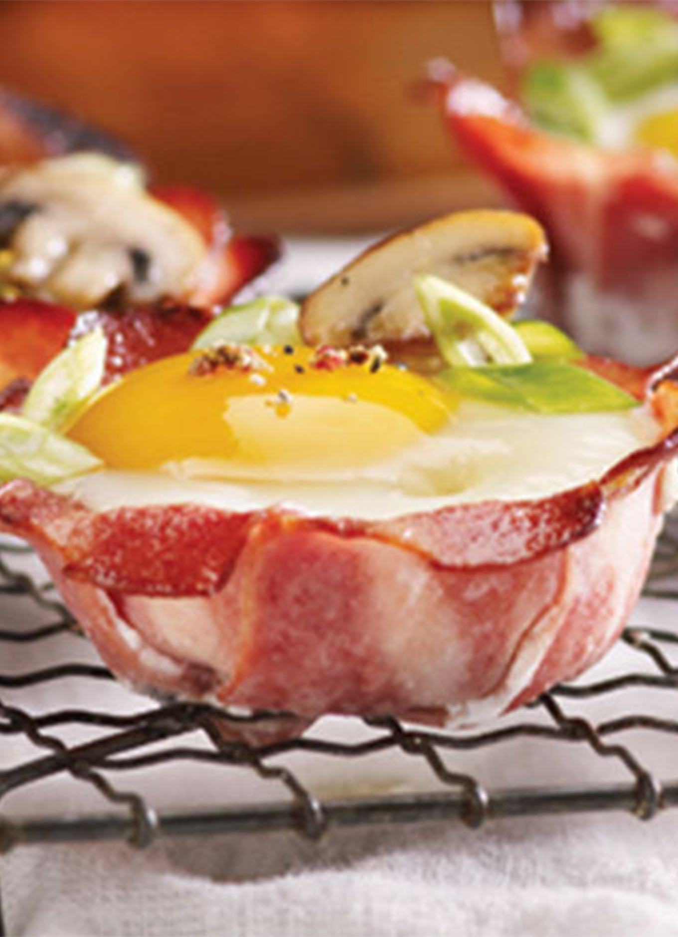 A tray of Breakfast Chicken Strips cups filled with eggs and topped with veggies.