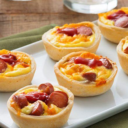 Un plateau de mini-quiches aux œufs, aux saucisses fumées de poulet halal et au fromage.