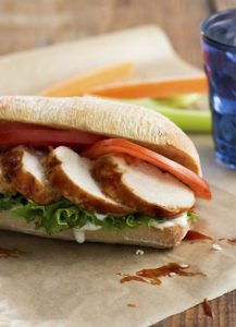 A fresh bun with generous slices of Grilled Buffalo Chicken with lettuce, tomato and sauce.