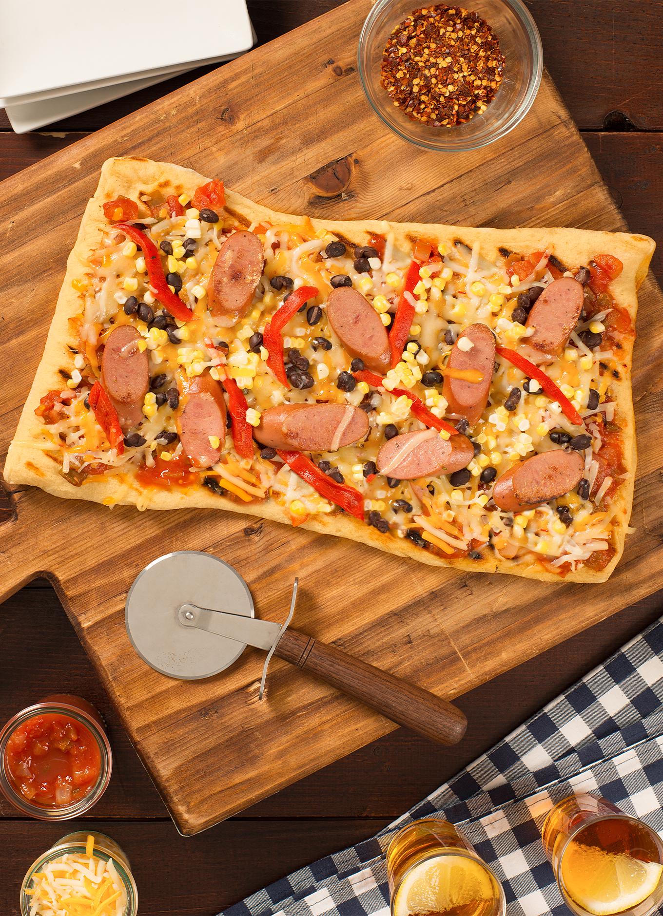 Une pizza maison garnie de saucisses au poulet halal, de maïs, de poivrons et de fromage sur un plateau de service.