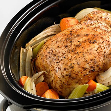 A whole cooked chicken resting in a slow cooker on a bed of celery, carrots, and onion.