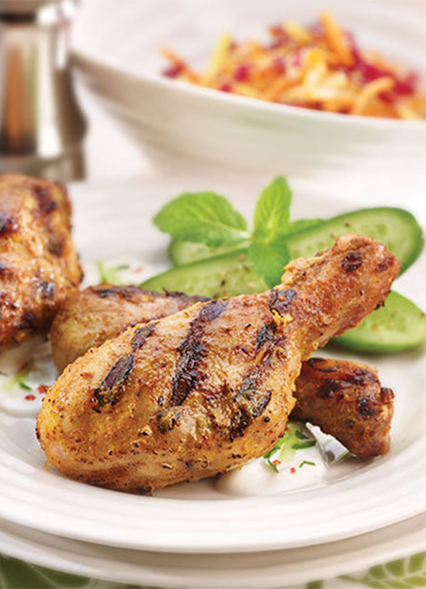 Grilled Indian Spiced BBQ Drumsticks plated with cucumber and mint, with yogurt dipping sauce