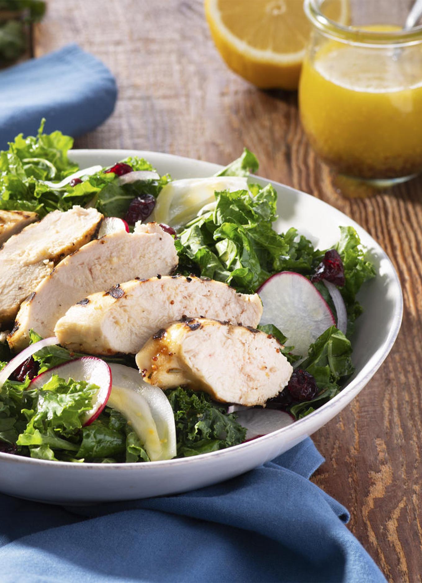 Un bol de salade verte, de radis tranchés et de lanières de poitrine de poulet grillée, à côté d'une serviette de table bleue, de couverts et d'un ramequin de vinaigrette.