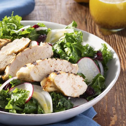 A bowl of salad greens, radish slices, and strips of barbecued chicken breast, beside a blue napkin, cutlery, and ramekin of salad dressing