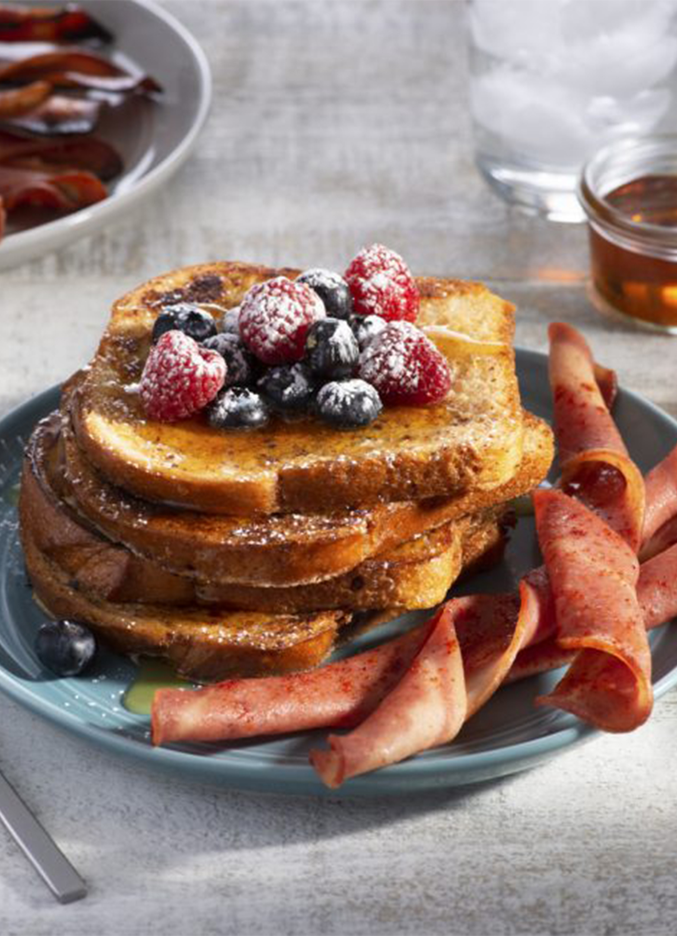 A stack of French Toast topped with syrup and fresh berries, served with a size of Breakfast Chicken Strip Twists