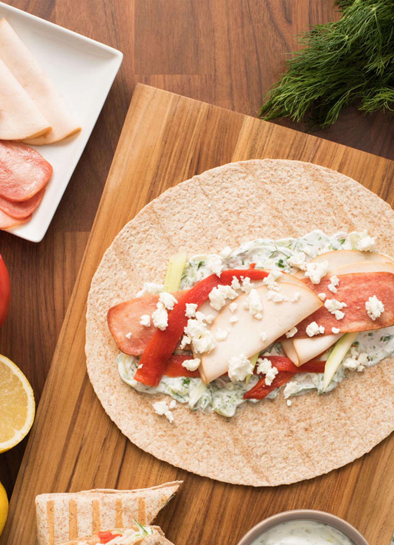 Une tortilla au poulet méditerranéen sur une planche à découper en bois accompagnée d'ingrédients frais.