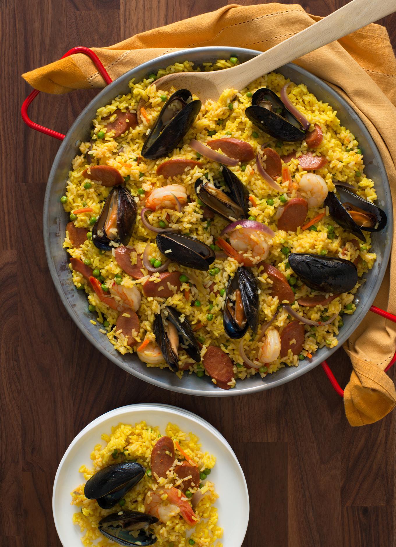 Un bol de paella recouvert de moules et de tranches de saucisses de Francfort au poulet halal