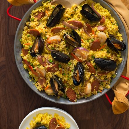 A bowl of Paella topped with mussels and sliced of Halal Chicken Franks
