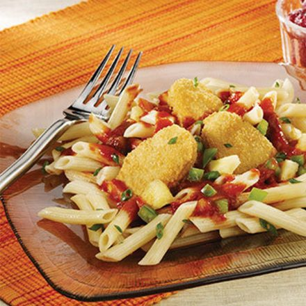 Pineapple Chicken Nuggets on a tropical bed of pasta with a side of fresh raspberries.