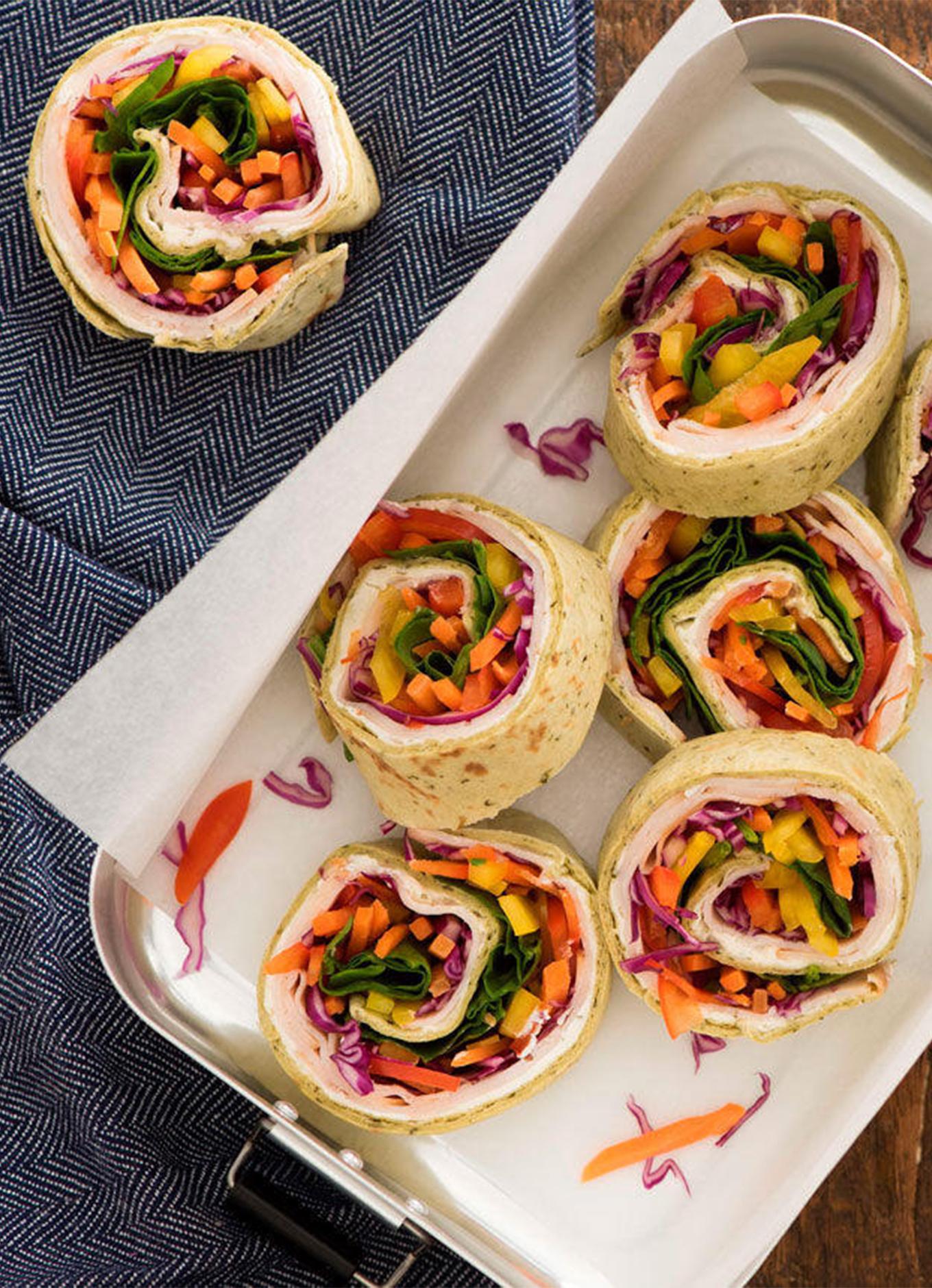 Un plateau haut en couleur de sandwichs en forme de spirales aux légumes arc-en-ciel, avec légumes colorés et poitrine de poulet fumée Zabiha Halal, servis sur une table en bois.