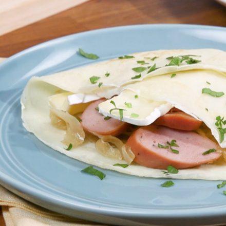 Une crêpe garnie de saucisses au poulet halal, de brie et d'oignons sautés servie sur une table pour le déjeuner.