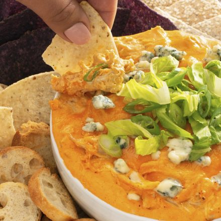 A bowl of Slow Cooker Buffalo Chicken Dip topped with green onions, surrounded by tortilla chips, pita chips, and crackers