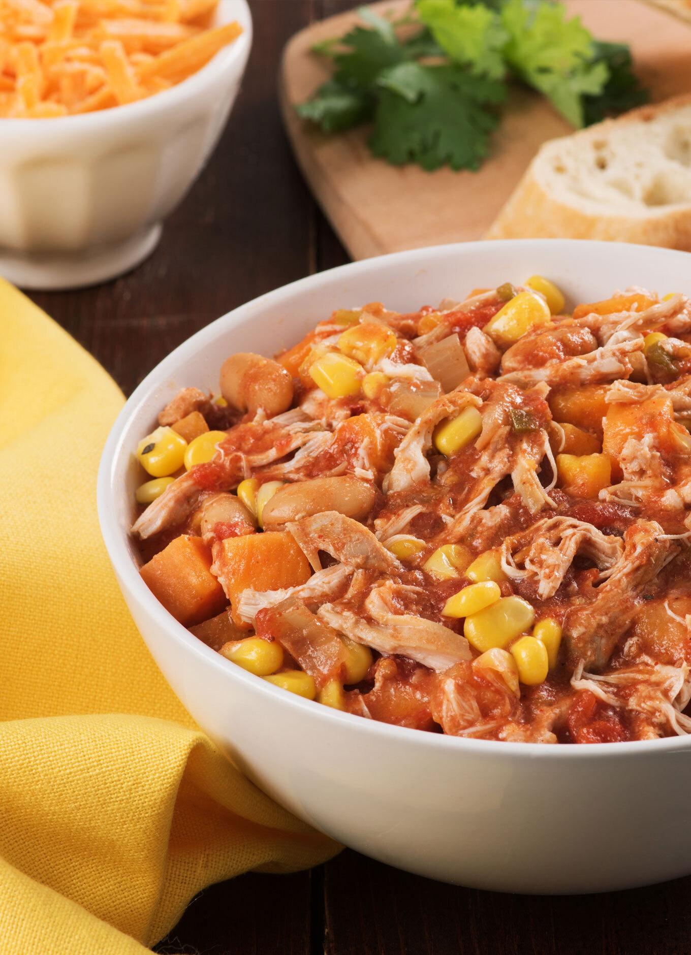 Un bol chaud de chili au poulet effiloché avec haricots blancs et maïs.