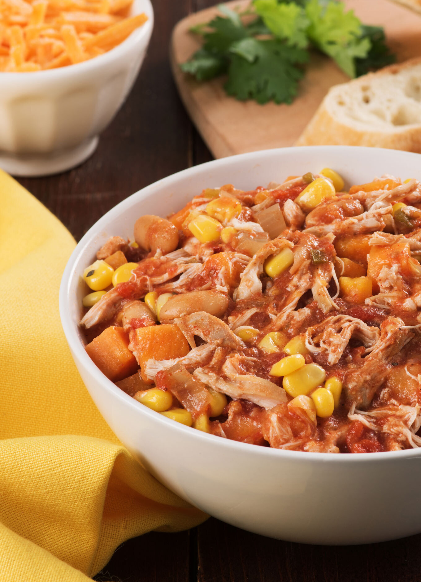 A steaming bowl of Slow Cooker Chicken & White Bean Chili with pulled chicken, corn, and white beans.