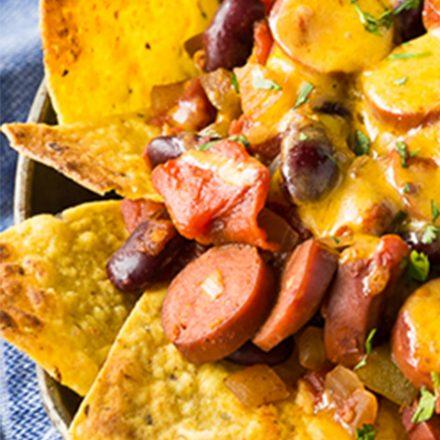 Un plateau de nachos au chili épicé, garni de tranches de saucisses de Francfort au poulet, de chili et de fromage fondu.