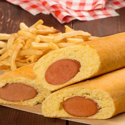 Trois saucisses sur bâtonnet placées sur une feuille de papier parchemin avec un accompagnement de frites et de ketchup