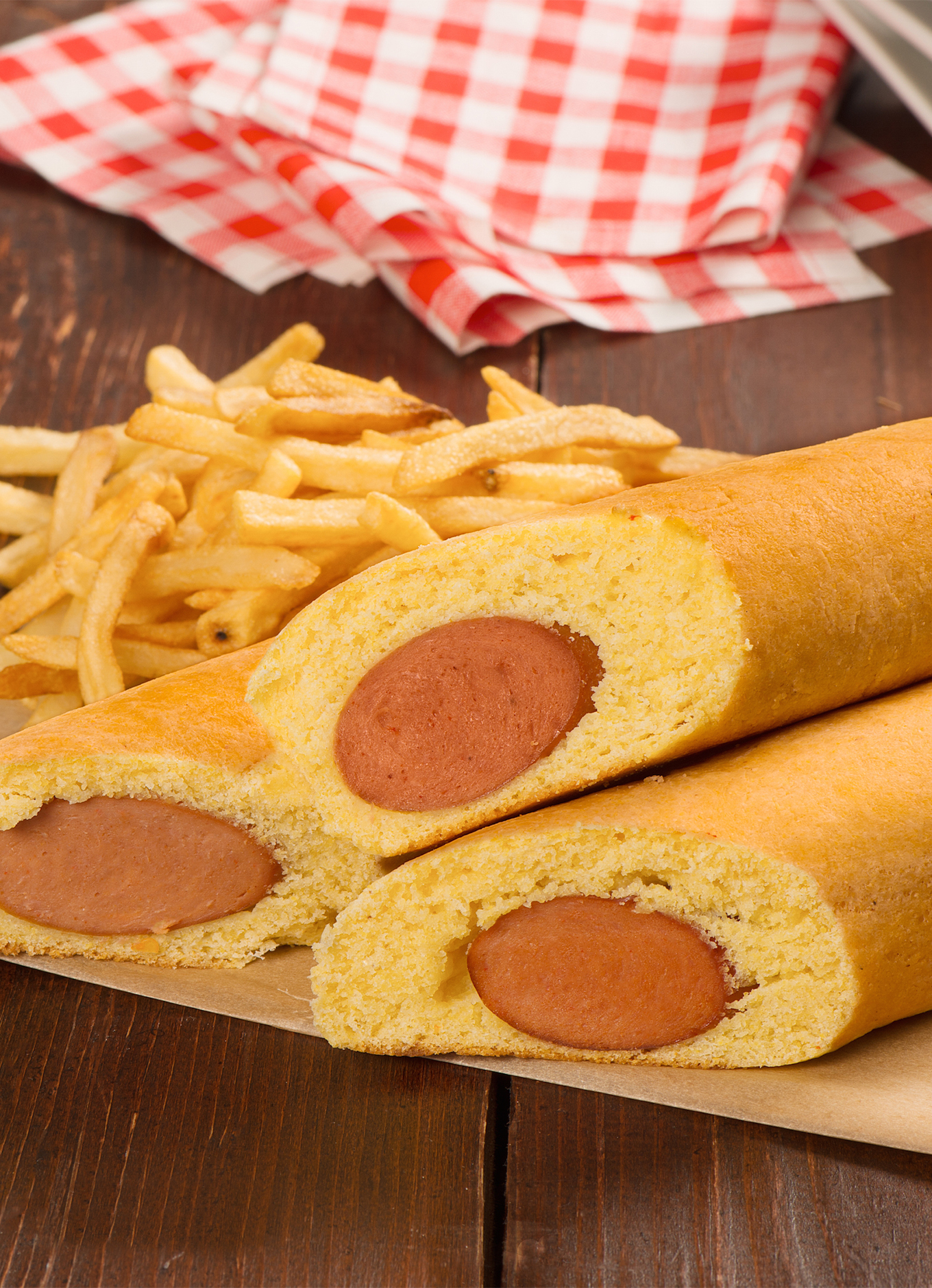 Three corn dogs on a sheet of parchment paper with a side of fries and ketchup for dipping