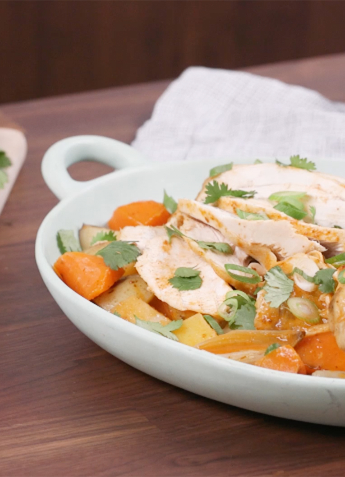 A platter with Thai Roasted Chicken resting on a bed of potatoes, parsnips and shallots