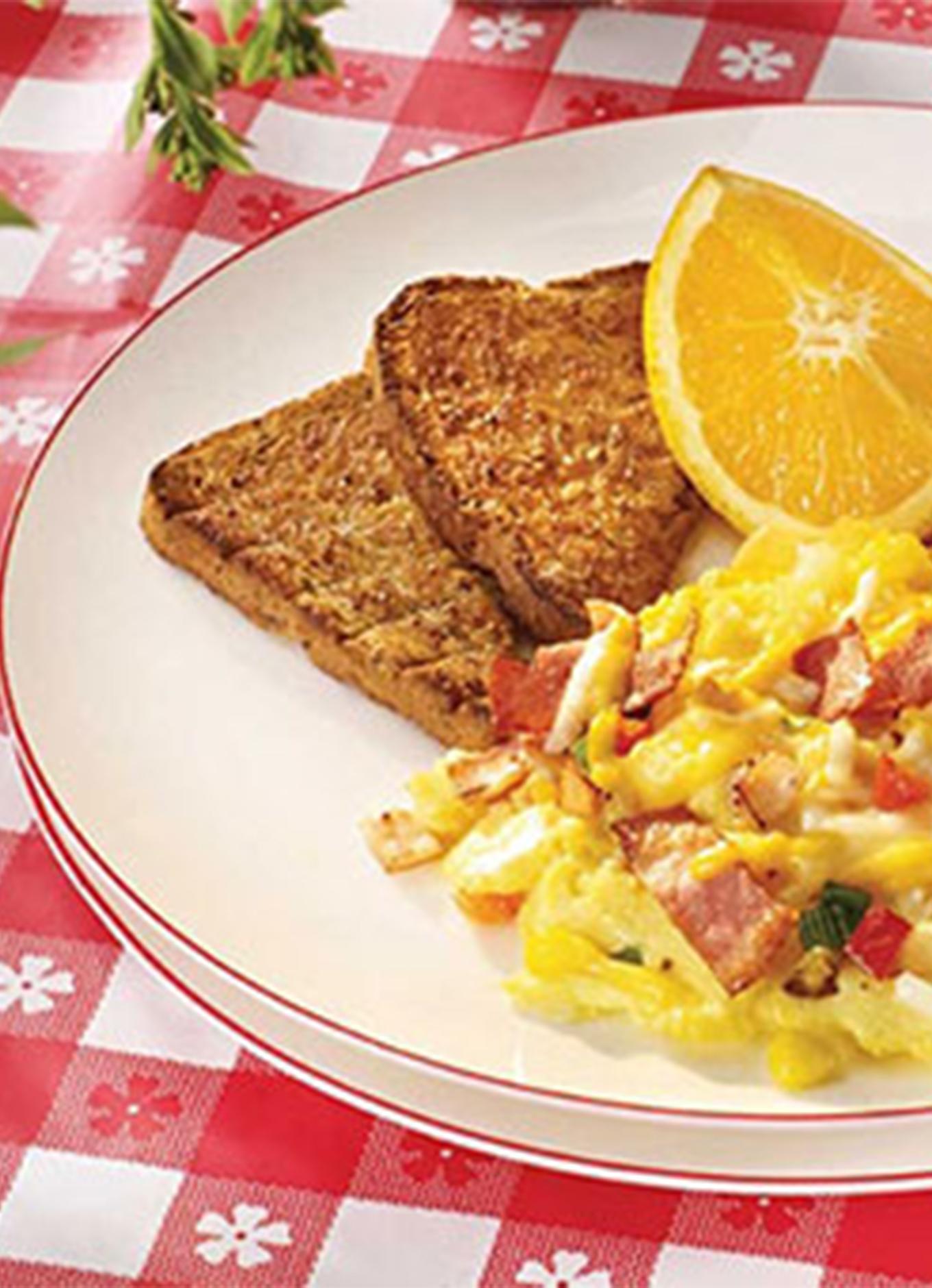 Un déjeuner de rôties, de fruits frais et d'œufs brouillés garnis de poivrons et de lanières de poulet pour déjeuner