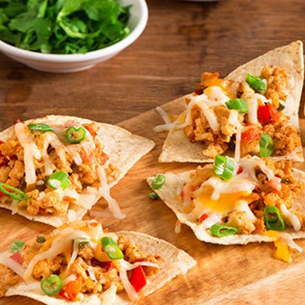 Un plateau de mini tacos de poulet halal garnis de fromage et d'oignons verts, servis avec de la coriandre et de la crème sure