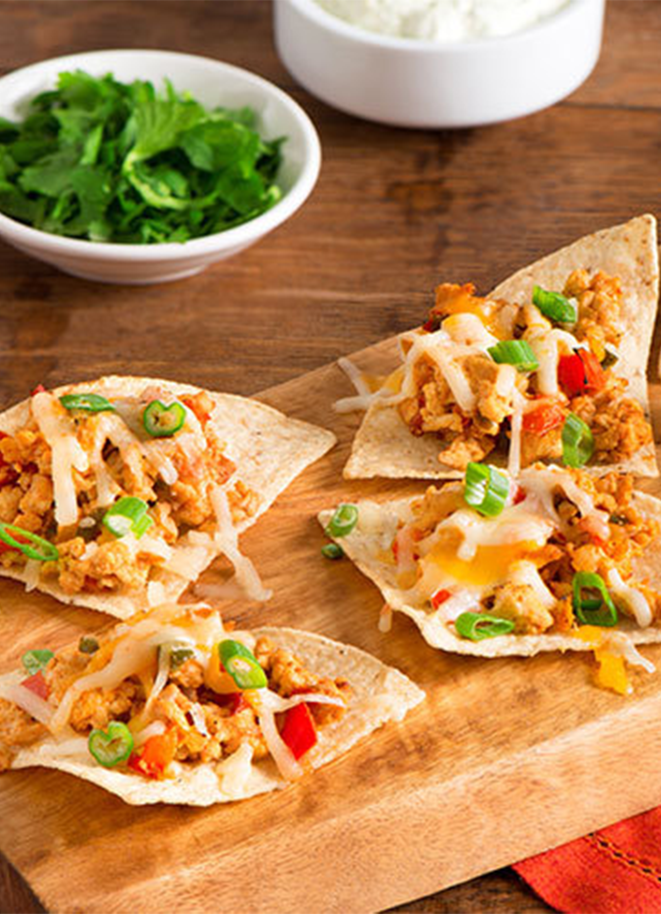A tray of mini CHalal Chicken Tacos topped with cheese and green onion, served with cilantro and sour cream