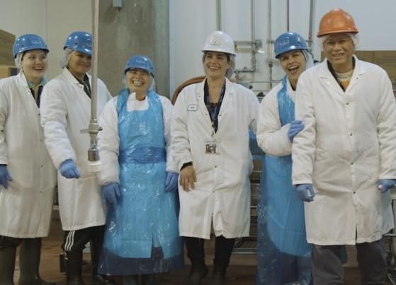Un groupe d'employés, tout sourire, portant l'équipement de protection dans une usine Zabiha Halal