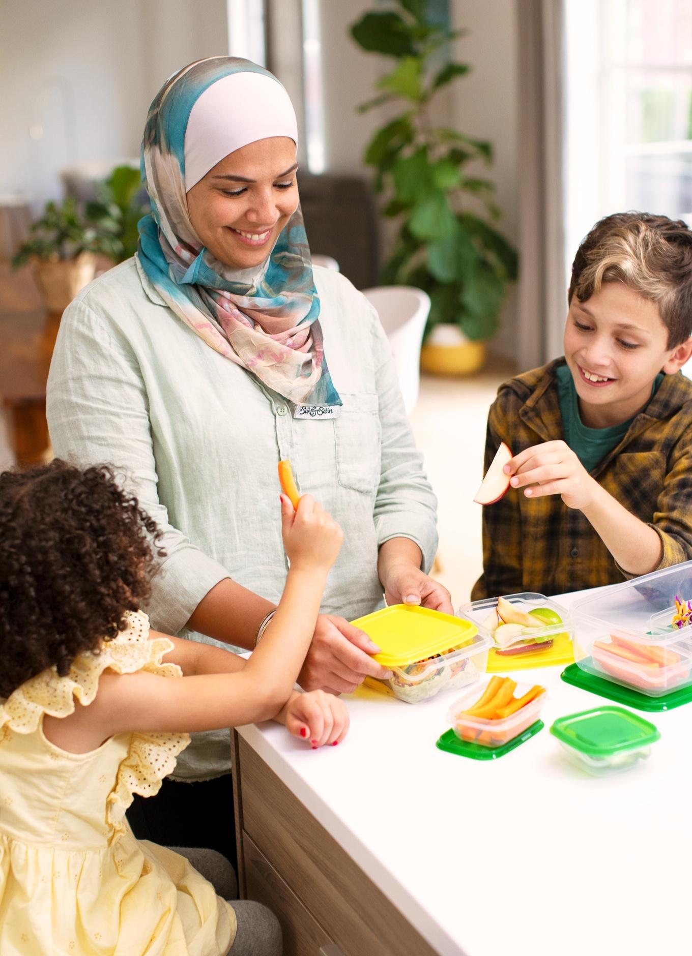 Deux enfants assis à la table d'une cuisine, qui savourent un dîner sain.
