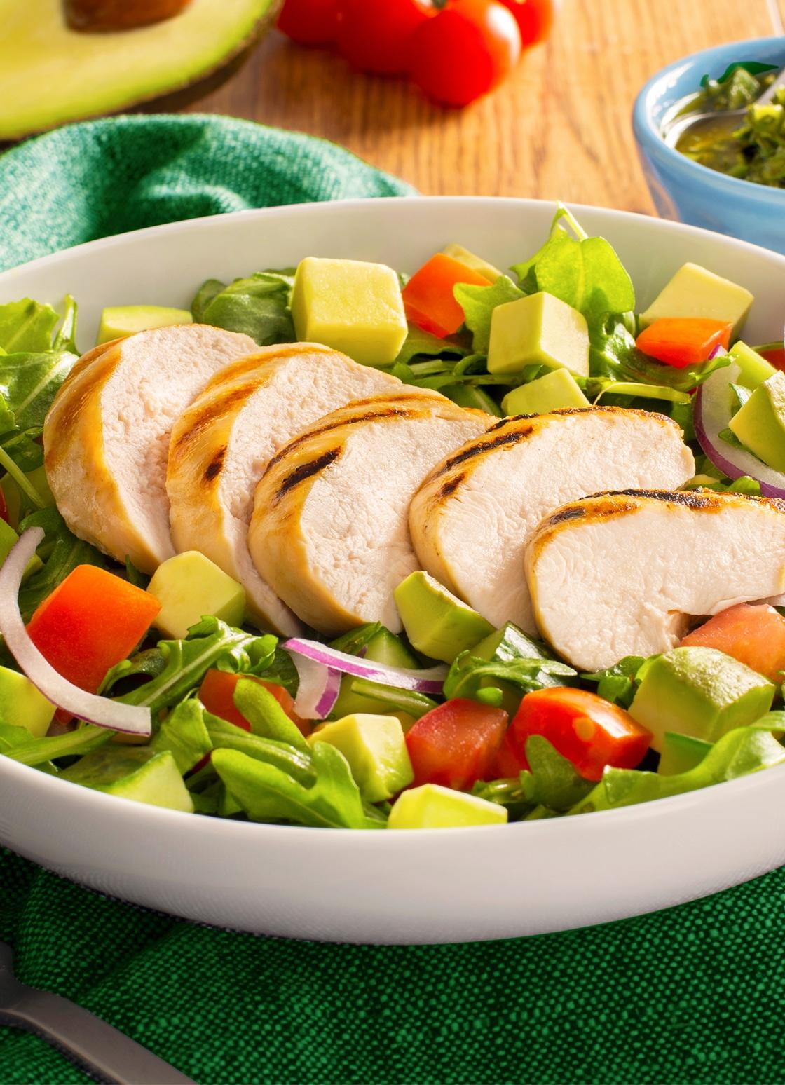 Un bol de salade composée de légumes feuilles, de tomates, d'avocat et d'oignon rouge, le tout garni d'épaisses tranches de poulet grillé.