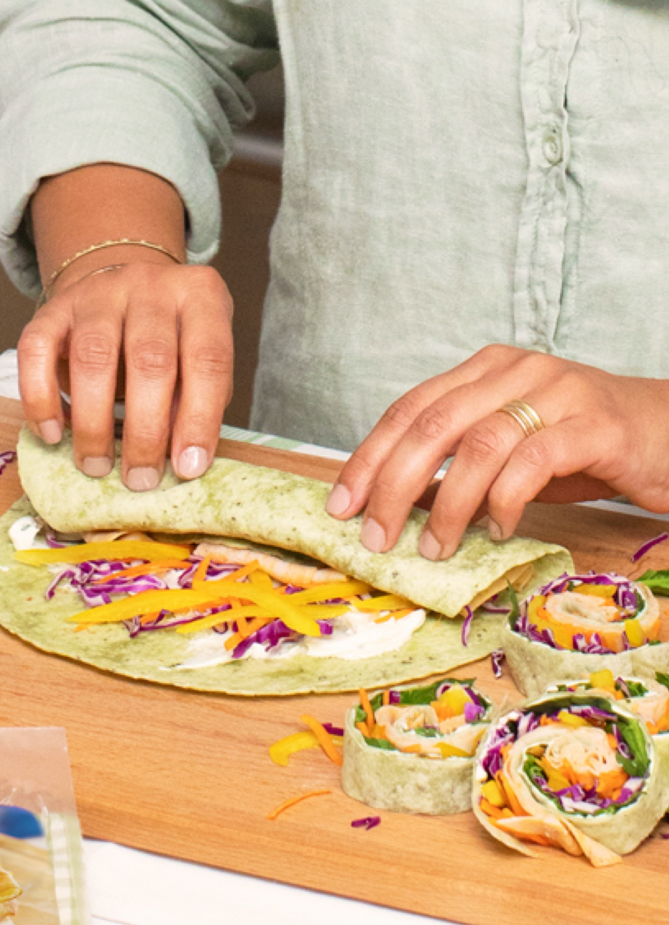 A person making colourful Rainbow Pinwheel Veggie Wraps with fresh vegetables and Halal Chicken Deli slices.
